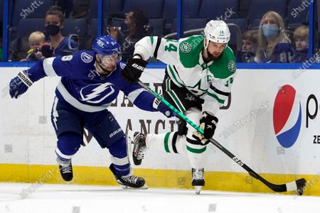 Dallas Stars left wing Jamie Benn (14) moves the puck ahead of Tampa Bay Lightning center Tyler Johnson (9) during the first period of an NHL hockey game, in Tampa, Fla