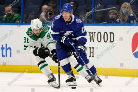 Tampa Bay Lightning left wing Ondrej Palat (18) moves the puck around Dallas Stars center Tyler Seguin (91) during the first period of an NHL hockey game, in Tampa, Fla