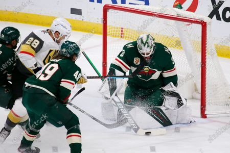 Minnesota Wild goaltender Cam Talbot (33) makes a stop on Vegas Golden Knights left wing William Carrier (28) as Minnesota Wild center Victor Rask (49) defends during the first period of an NHL hockey game, in St. Paul, Minn