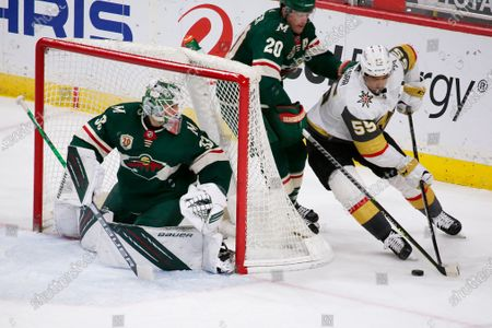 Vegas Golden Knights right wing Keegan Kolesar (55) brings the puck around the goal as Minnesota Wild's Ryan Suter (20) and goaltender Cam Talbot (33) defend during the first period of an NHL hockey game, in St. Paul, Minn