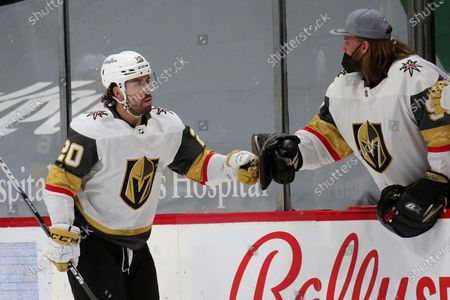 Vegas Golden Knights center Chandler Stephenson (20) is congratulated by goaltender Robin Lehner after scoring against the Minnesota Wild during the second period during an NHL hockey game, in St. Paul, Minn