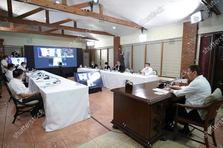 In this photo provided by the Malacanang Presidential Photographers Division, Philippine President Rodrigo Duterte, right, presides over a meeting with the Inter-Agency Task Force on the Emerging Infectious Diseases (IATF-EID) core members at the Malacanang presidential palace in Manila, Philippines . The Philippine president has asked China to get back 1,000 doses of donated Sinopharm vaccine after facing criticisms for allowing himself to be injected with it although it has not yet been authorized for public use in the country