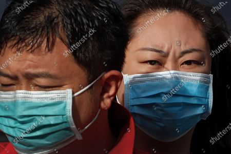 Stock Picture of People wearing face masks to help curb the spread of the coronavirus ride on a scooter on a street in Beijing