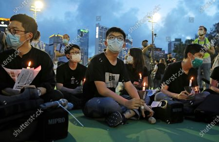 In this June 4, 2020, photo, democracy activist Joshua Wong, center, and Nathan Law, left, hold candles during a vigil to remember the victims of the 1989 Tiananmen Square Massacre at Victoria Park in Hong Kong. Wong received a new prison sentence, for going out to mark the Tiananmen crackdown anniversary last year