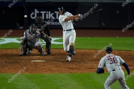 New York Yankees' Giancarlo Stanton hits an RBI single during the eighth inning of a baseball game against the Houston Astros, in New York. The Yankees won 6-3