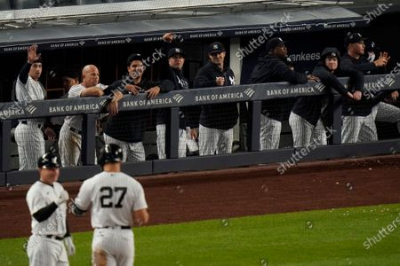 New York Yankees players gesture to Giancarlo Stanton (27) after stanton drove in a run with a single during the eighth inning of a baseball game against the Houston Astros, in New York. The Yankees won 6-3