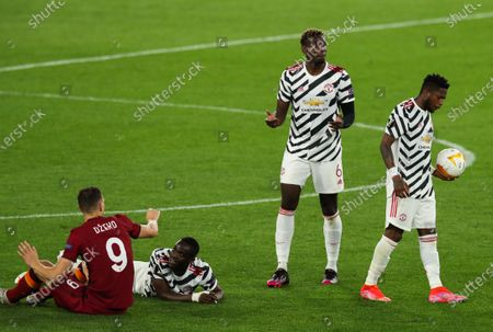 Edin Dzeko of Roma fouls Eric Bailly of Manchester United as Paul Pogba looks on