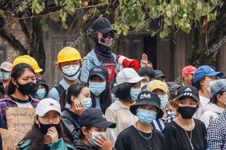 An anti-military coup protester is seen wearing a ghost mask while holding a megaphone during the protest.