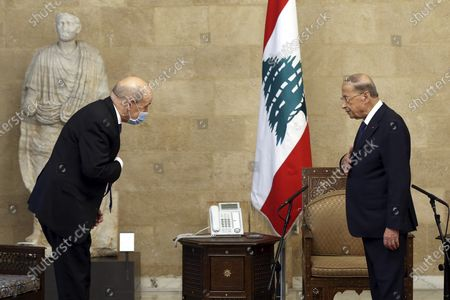 """In this photo released by Lebanon's official government photographer Dalati Nohra, French Foreign Minister Jean-Yves Le Drian, left, and Lebanese President Michel Aoun, greet each other at the Presidential Palace in Baabda, east of Beirut, Lebanon, . Le Drian began a visit to Lebanon Thursday with a message of """"great firmness"""" to its political leaders, threatening to take additional measures against officials obstructing the formation of a government in the crisis-hit country"""