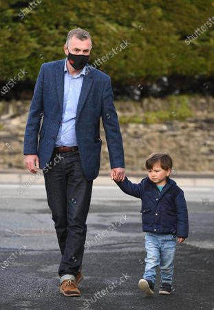 Plaid Cymru leader Adam Price on his way to vote in the Senedd election with his son at his local polling station Pontargothi Memorial Hall, Pontargothi, Carmarthen.