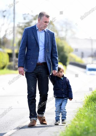 Stock Image of Plaid Cymru leader Adam Price on his way to vote in the Senedd election with his son at his local polling station Pontargothi Memorial Hall, Pontargothi, Carmarthen.