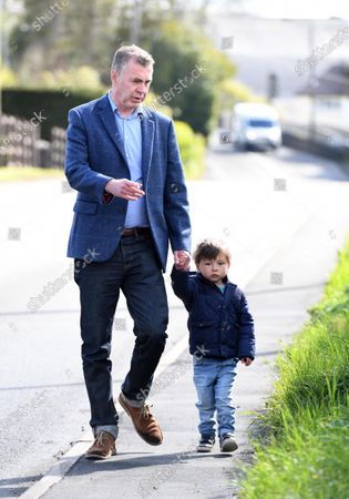 Stock Photo of Plaid Cymru leader Adam Price on his way to vote in the Senedd election with his son at his local polling station Pontargothi Memorial Hall, Pontargothi, Carmarthen.