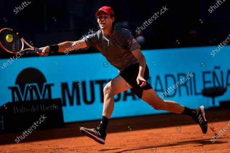 Australia's Alex de Minaur returns the ball to Dominic Thiem of Austria during their match at the Mutua Madrid Open tennis tournament in Madrid, Spain