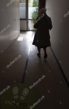 Woman follows a blue line toward a cubicle as she prepares to receive the Johnson & Johnson COVID-19 vaccination at a social center in Antwerp, Belgium, . Antwerp has opened several satellite vaccination centers in areas of the city where people have less ability or means to make it to the larger centers