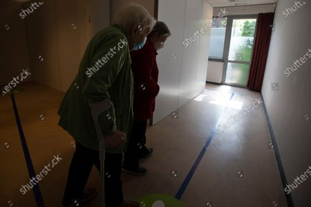 Two women follow a a blue line toward a cubicle as they prepare to receive the Johnson & Johnson COVID-19 vaccination at a social center in Antwerp, Belgium, . Antwerp has opened several satellite vaccination centers in areas of the city where people have less ability or means to make it to the larger centers