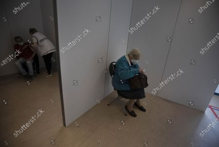 Man, left, receives the Johnson & Johnson COVID-19 vaccination as a woman waits in another cubicle at a social center in Antwerp, Belgium, . Antwerp has opened several satellite vaccination centers in areas of the city where people have less ability or means to make it to the larger centers
