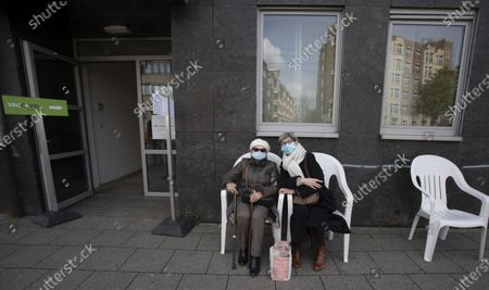 Two women pose outside of a social center after one woman received the Johnson & Johnson COVID-19 vaccination in Antwerp, Belgium, . Antwerp has opened several satellite vaccination centers in areas of the city where people have less ability or means to make it to the larger centers