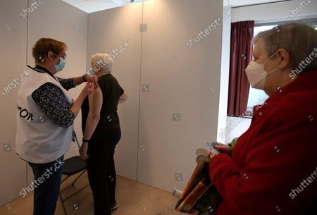 Woman receives the Johnson & Johnson COVID-19 vaccination as her friend, right, waits at a social center in Antwerp, Belgium, . Antwerp has opened several satellite vaccination centers in areas of the city where people have less ability or means to make it to the larger centers