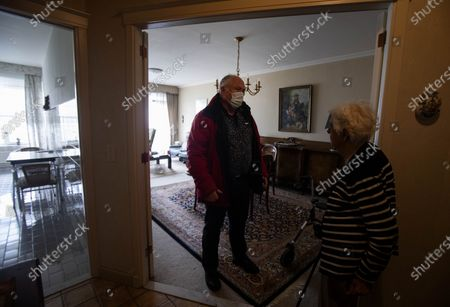 Belgian doctor Peter Theerens, left, speaks with an elderly patient as he arrives on a house call to administer the Johnson & Johnson COVID-19 vaccine in Antwerp, Belgium, . Antwerp has opened several small satellite vaccination centers and sent doctors out on house calls to administer the vaccine to patients who are unable to travel to the larger centers