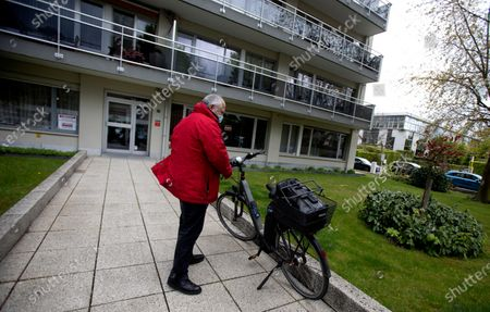 Belgian doctor Peter Theerens arrives with his medical bag on his bicycle to administer the Johnson & Johnson COVID-19 vaccine to an elderly patient in Antwerp, Belgium, . Antwerp has opened several small satellite vaccination centers and sent doctors out on house calls to administer the vaccine to patients who are unable to travel to the larger centers