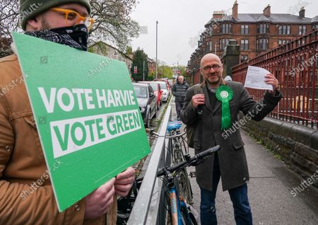 Scottish Green Party Co-leader Patrick Harvie holds his polling card before casting his vote at the polling station at Notre Dame Primary School in the west end of Glasgow today.
