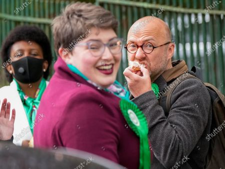 Scottish Green Party Co-leader Patrick Harvie enjoys a doughnut outside the polling station at Notre Dame Primary School in the west end of Glasgow after casting his vote on Scottish Election Day.
