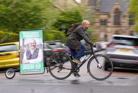 Scottish Green Party Co-leader Patrick Harvie with an advertising bicycle outside the polling station at Notre Dame Primary School in the west end of Glasgow after casting his vote on Scottish Election Day.