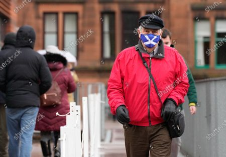 A male voter wears a saltire flag face mask outside the polling station at Notre Dame Primary School in the west end of Glasgow on Scottish Election Day.