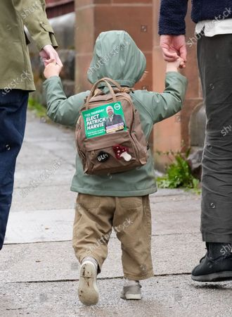 "A young boy wears a ""Vote Green"" sign on his backpack as he walks hand in hand with his parents outside the polling station at Notre Dame Primary School in the west end of Glasgow on Scottish Election Day."