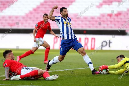 Mehdi Taremi of FC Porto (C ) vies with Benfica's goalkeeper Helton Leite (R ) during the Portuguese League football match between SL Benfica and FC Porto at the Luz stadium in Lisbon, Portugal on May 6, 2021.