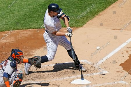 New York Yankees designated hitter Giancarlo Stanton (27) hits a solo home run during the third inning of a baseball game against the Houston Astros, at Yankee Stadium in New York. Astros catcher Martin Maldonado (15) works behind the plate