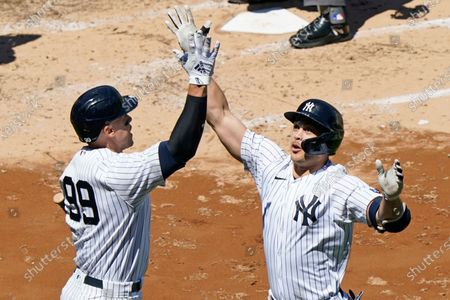 On-deck batter New York Yankees' Aaron Judge, left, celebrates with the Yankees designated hitter Giancarlo Stanton after Stanton hit a solo home run during the third inning of a baseball game against the Houston Astros, at Yankee Stadium in New York