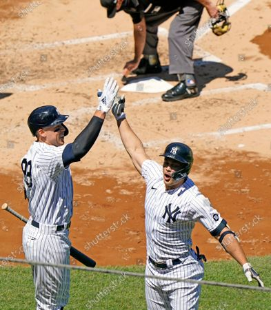 On-deck batter New York Yankees Aaron Judge, left, celebrates with Yankees designated hitter Giancarlo Stanton after Stanton hit a solo home run during the third inning of a baseball game against the Houston Astros, at Yankee Stadium in New York
