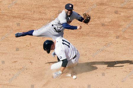 Houston Astros second baseman Jose Altuvé, top, throws to first after forcing out New York Yankees' Brett Gardner (11) after Yankees designated hitter Giancarlo Stanton hit into a baseball game-ending double play, at Yankee Stadium in New York