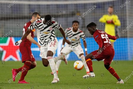 Manchester United's Eric Bailly, center, fights for the ball with Roma's Henrikh Mkhitaryan, left, and Roma's Ebrima Darboe during the Europa League semifinal, second leg soccer match between Roma and Manchester United at Rome's Olympic stadium, Italy