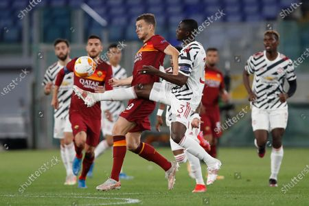 Roma's Edin Dzeko, left, is challenged by Manchester United's Eric Bailly during the Europa League semifinal, second leg soccer match between Roma and Manchester United at Rome's Olympic stadium, Italy