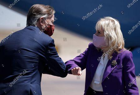 Sen. John Hickenlooper, D-Colo., greets first lady Jill Biden as she arrives at the Colorado Springs Airport, in Colorado Springs, Colo