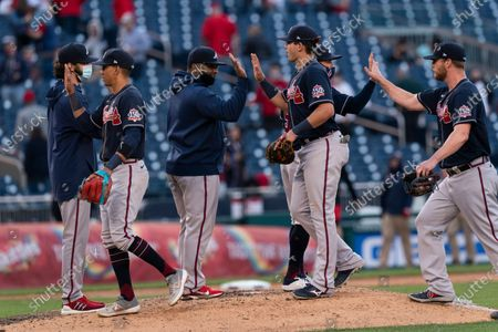 Atlanta Braves' third baseman Ehire Adrianza, front left to right, third baseman Austin Riley and relief pitcher Will Smith, celebrate with teammates after winning a baseball game against the Washington Nationals in Washington