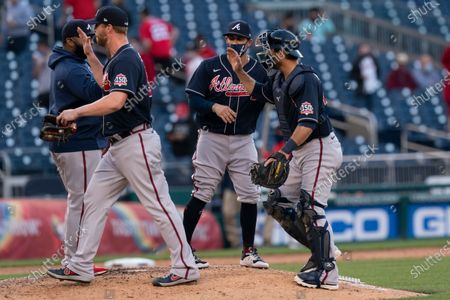 Atlanta Braves catcher Jeff Mathis, right, and relief pitcher Will Smith, left, celebrate with teammates after winning 3-2 a baseball game against the Washington Nationals in Washington