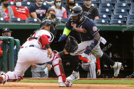 Atlanta Braves left fielder Marcell Ozuna (R) attempts to run past Washington Nationals catcher Yan Gomes (L) in the fourth inning of the MLB baseball game between the Washington Nationals and Atlanta Braves at Nationals Park in Washington, DC, USA, 06 May 2021.