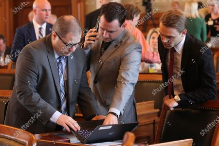 Kansas state Reps. Nick Hoheisel, left, R-Wichita; Blake Carpenter, center, R-Derby, and Avery Anderson, R-Newton, confer on the House floor ahead of the chamber's debate on a bill legalizing the medical use of marijuana, at the Statehouse in Topeka, Kan. Carpenter led the debate for supporters, and all three voted for the measure, which has passed