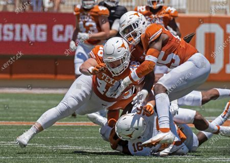 Texas defenders Jake Ehlinger, left, and B.J. Foster, right, tackle Kayvontay Dixon (16) during the first half of the Orange and White spring scrimmage college football game in Austin, Texas. Ehlinger, the younger brother of former Longhorns quarterback Sam Ehlinger, was found dead near campus Thursday, May 6, Austin police said. Officers found the 20-year-old Ehlinger after responding to a call at 12:18 p.m. Police did not detail how they found him but said the death is not considered suspicious. No cause of death was immediately released