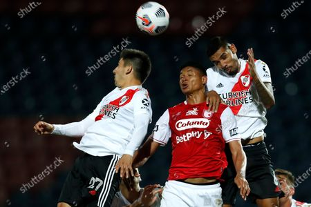 Cristian Fontana, left, and Hector Martinez, right, of Argentina's River Plate fight for the ball with Jorge Ramos of Colombia's Independiente Santa Fe during a Copa Libertadores soccer match in Asuncion, Paraguay