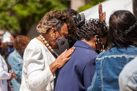 Gwen Carr (left), mother of Eric Garner, Valerie Bell (center), mother of Sean Bell, and Darlene Cain (right), mother of Dale Graham, all of whom were killed by police, listen to the music of gospel singer Robin Sugar Williams during a rally in which mothers of children who died at the hands of police demand justice, accountability, and a complete overhaul of policing in the United States.