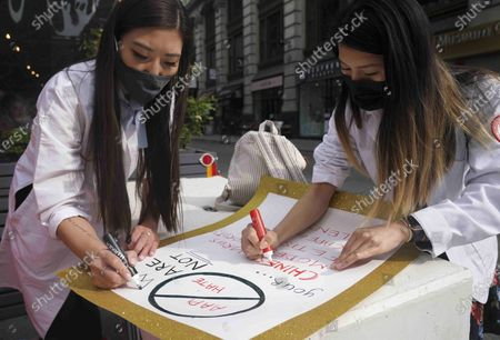 Dr. Michelle Lee, left, a radiology resident, and Ida Chen, right, a physician assistant student, prepare posters they carry at rallies protesting anti-Asian hate, in New York's Chinatown. Lee, who is Korean-born, and Chen, who is American-born Chinese, join medical professionals of Asian and Pacific Island descent who feel the anguish of being racially targeted because of the virus while toiling to keep people from dying of it