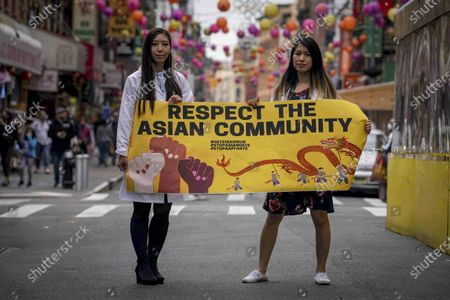 Dr. Michelle Lee, left, a radiology resident, and Ida Chen, right, a physician assistant student, unfold a banner Lee created to display at rallies protesting anti-Asian hate, in New York's Chinatown. Lee, who is Korean-born, and Chen, who is American-born Chinese, join medical professionals of Asian and Pacific Island descent who feel the anguish of being racially targeted because of the virus while toiling to keep people from dying of it