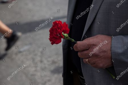 Dimitris Koutsoumpas, the general secretary of communist party (KKE) wearing a protective face mask holds a red carnation, Kurdish wearing protective face masks hold Ocalan flags,  as he protests during a rally commemorating May Day in Athens, Greece on May 6, 2021.