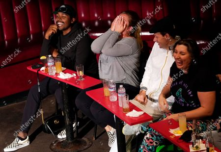Group of friends share laughter during a performance by stand-up comedian Sherri Shepherd at the re-opening of the Laugh Factory comedy club, in Los Angeles. The club has been closed to live audiences since March 2020 due to the COVID-19 pandemic