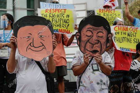 Protesters wear a mask of Philippine President Rodrigo Duterte and Chinese President Xi Jinping during a rally outside the Chinese consulate in Metro Manila, Philippines on . The group is demanding China to get out of Philippine-claimed territory in the South China Sea