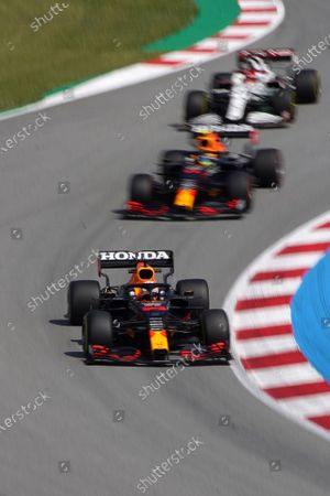 Red Bull driver Max Verstappen of the Netherlands leads Red Bull driver Sergio Perez of Mexico and Alfa Romeo driver Kimi Raikkonen of Finland, background, through a curve during the second free practice for the Spanish Formula One Grand Prix at the Barcelona Catalunya racetrack in Montmelo, just outside Barcelona, Spain, . The Spanish Grand Prix will be held on Sunday
